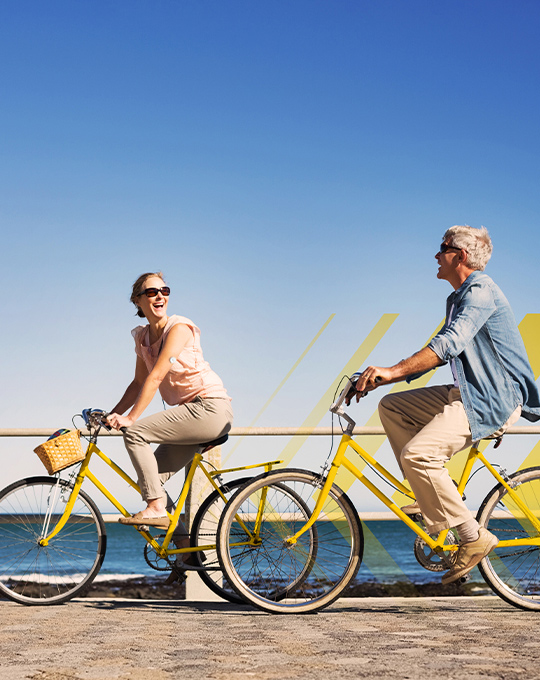 Image of a woman wearing a FreeStyle Libre sensor and biking with a man along the ocean