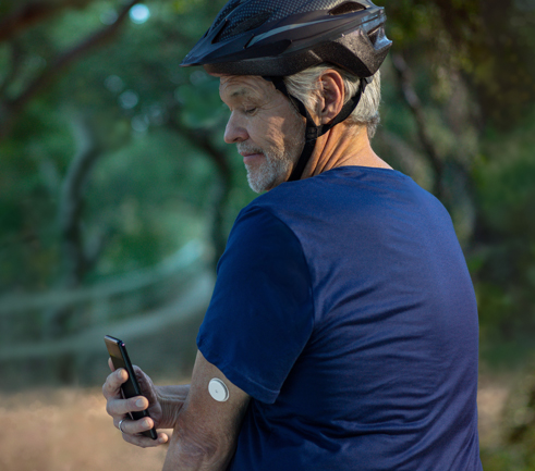 Image of a man scanning his FreeStyle Libre continuous glucose monitoring sensor.