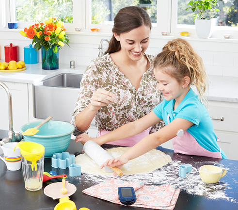 Parent baking with child wearing a FreeStyle Libre continuous glucose monitor on upper arm